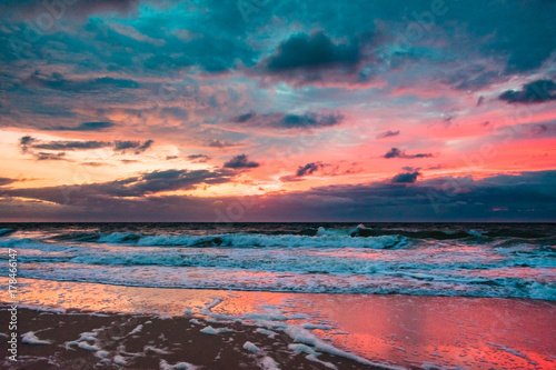 Foto op Canvas Lavendel colorful clouds reflecting off the water as waves crash on shore and the sun rises on the horizon