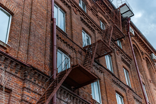 Metal ladder on old brick facade - 178469562