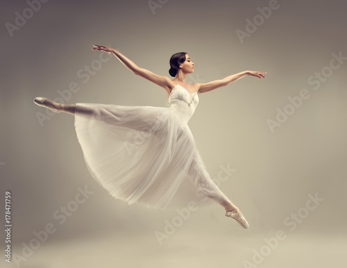 Ballerina. Young graceful woman ballet dancer, dressed in professional outfit, shoes and white weightless skirt is demonstrating dancing skill. Beauty of classic ballet. © Sofia Zhuravetc
