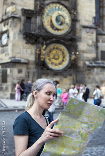 the woman watches the map of the city on background of historical medieval astronomical Clock on the Old Town Hall in Prague, Czech Republic Poster