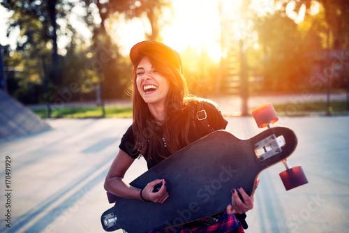 Fotobehang Skateboard Cute urban girl holding skateboard in skatepark - hipster style photo