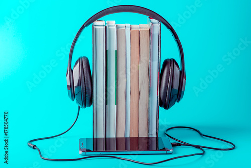 Fotobehang Muziek Phone with black headphones with a stack of books on a blue background. Concept of audiobooks and modern education