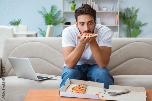 Man eating pizza having a takeaway at home relaxing resting - 178505725