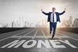 Businessman running towards money on track