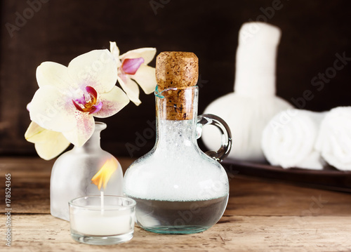 Fotobehang Spa Spa set on wooden table. Yellow orchid and lavender bath foam. White towels and Thai massage bags in background. Relax, massage concept. Text space