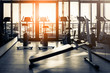 Elliptical in Modern gym interior with equipment. Row of training exercise bikes wheel detail, backlight. Healthy lifestyle concept