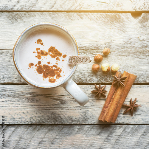 Foto op Aluminium Milkshake Hot cocoa drink in rustic mug. Cinnamon sticks and anise stars on wooden table. Christmas cozy scene. Top view.