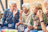 Group of aged friends spending pleasant time together at backyard party: they chatting animatedly with each other, drinking red wine and eating fresh fruits - 178542722