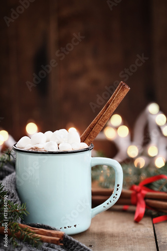 Foto op Canvas Chocolade Enamel cup of hot cocoa with mini marshmallows and cinnamon bark. Pine boughs and gray scarf against a rustic background with beautiful Christmas lights of bokeh.