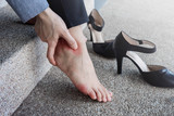 Health Care concept. Female Suffering from Pain in Ankle or Foot, Effect from Hard Walking or Comfortable Shoes, Barefoot Business Woman sitting at stair, High Heels as background - 178549341