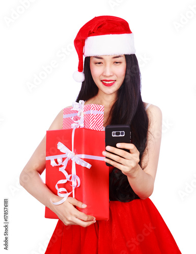 woman in Santa Claus clothes looking at mobile phone with gift box isolated on w Poster