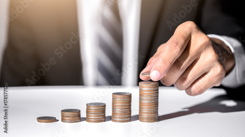 Hand of male putting gold coin stack, Finance and investment save money concept