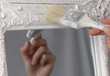Diy woman painting, renewing mirror frame at home.