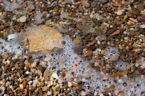 Foto op Aluminium Stenen in het Zand Stone pebble background with sea foam.Wet colorful stones. Seaside pebble natural ornament. Wet pebbles mosaic. View from above. Fragment of beach pebble with small colored pebbles