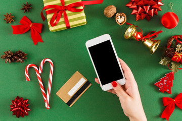 Girl buying christmas presents online on smartphone with credit card