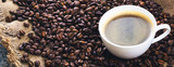 Fried coffee beans. Coffee mug on the background of coffee beans. Panorama, banner.