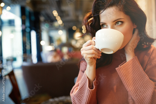 Poster woman drinking coffee in a cafe
