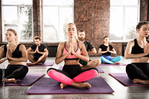 Yoga meditation of young people in lotus pose in fitness center Poster
