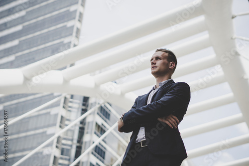 Portrait of happy businessman standing on front of business center.