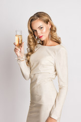 Pretty sexy blonde woman on white background. Beautiful young lady in beige glitter sequins long evening dress looking over shoulder. Glass of champagne in hand. Curly hair, makeup