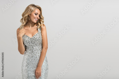 Beautiful woman in shining silver dress on gray background. Poster