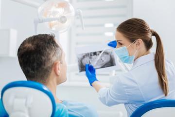 Nice joyful dentist pointing at the Xray photo