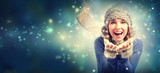 Happy young woman blowing snow in snowy night - 178665975