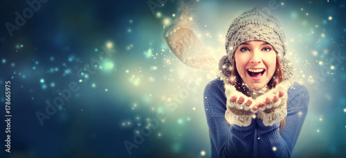 Happy young woman blowing snow in snowy night