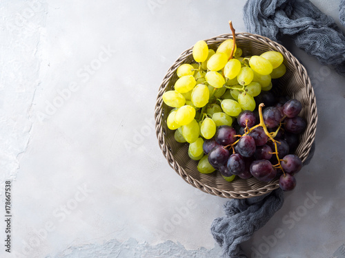 White and dark grapes in a basket on gray. Abstract minimal fruit still life - 178667538