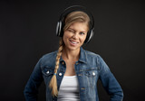 Portrait of hipster woman wearing earphones on black background.  - 178668385