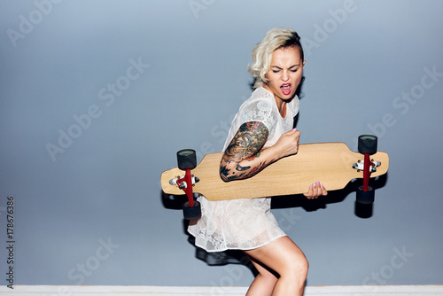 Tattooed pretty blond girl goofing around, playing longboard as guitar and singi Poster