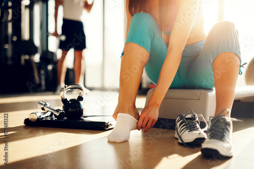 Poster Close up of young athletic girl putting on socks and preparing for new exercise day in the gym.