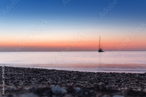 Plexiglas Lichtroze Twilight before sunrise with calm sea with silhouette of yacht