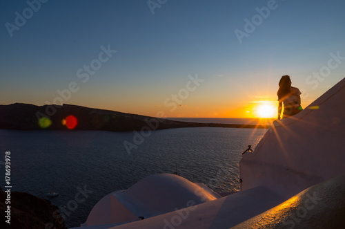 View of Santorini sunset from Oia town with silhouette of girl Poster