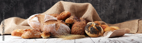 Assortment of baked bread and bread rolls on wooden table background. - 178694515
