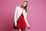 Fashion portrait of young woman in pink leather jacket and red dress.