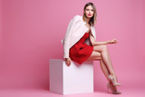 Fashion portrait of young woman in pink leather jacket and red dress. - 178695564
