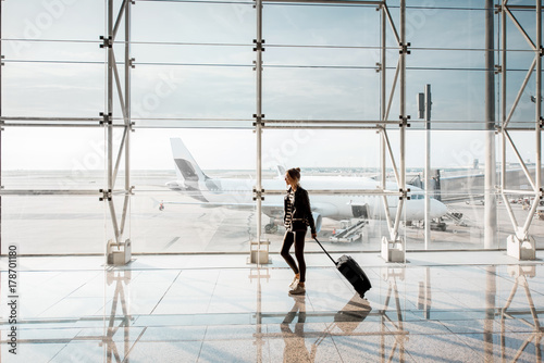View on the aiport window with woman walking with suitcase at the departure hall of the airport. Wide angle view with copy space