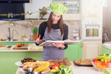 Pretty young female cook wearing Chef s hat looking for a recipe in cookbook standing in the kitchen - 178710154