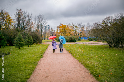 Juliste Two girls with red and blue umbrella stand stand in the autumn the track and talk to the autumn landscape