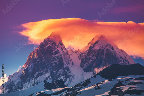Colorful sunset over the snowy mountain peaks with dramatic overcast pink clouds sky. Travel nature background. Holiday, sport, recreation. Kazbegi National Park, Gergeti, Georgia. Retro toning filter