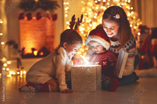 Merry Christmas! family mother and children with magic  gift  at home - 178730773
