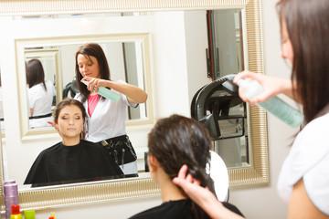 Hairdresser spraying conditioner on woman hair