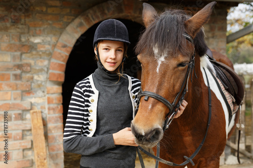 Teenage girl with her horse in front of a stable Poster