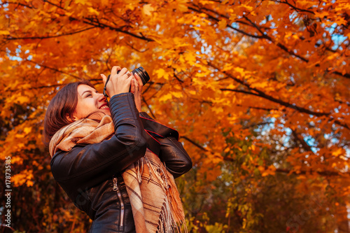 Fotobehang Rood traf. Young photographer takes pictures of autumn forest