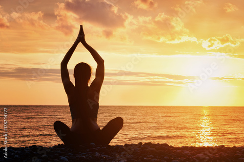 Poster Girl is practicing yoga on the beach. View from the back, sunset, silhouettes