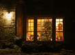 Welcome home Christmas tree.Outdoor close up view of old style brick house window with decorated and glowing christmas tree. Night scene. Christmas and New Year holiday background.