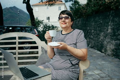 Senior woman drinks cofee and sitting on outdoors cafe with laptop Poster