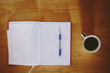 Red notebook and cup of coffee on a office desk - 178777595
