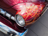 Classic American custom muscle car with flames painted behind headlight